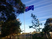 Australian flag flying on pole in front of residential home Royalty Free Stock Image