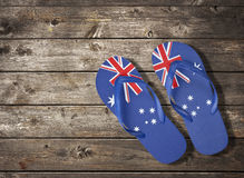 Australian Flag Thongs Wood Background. Thongs with an Australian flag pattern resting on a rustic wood background stock photography