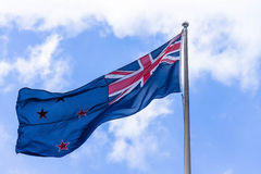 Australian flag waving against a blue sky with white clouds Stock Images