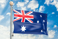 Australian flag waving in blue cloudy sky, 3D rendering Stock Images