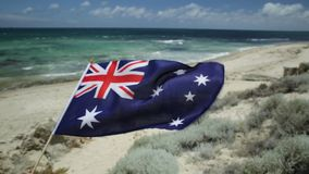Tourism in Australia. Australian flag waving on the foreground with coastal landscape of Mettams Pool, Trigg Beach, North Beach near Perth in Western Australia stock video footage