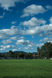 Australian football field with clouds Stock Photos
