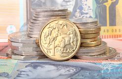 Australian dollar coin on currency background. An Australian gold one dollar coin sits next to a stack of coins on top of Australian bank notes Stock Image