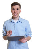 Australian guy with tablet computer looking at camera Stock Photo