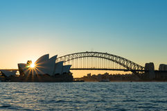 Australian Harbour Bridge at sunset. Australian iconic Harbour Bridge silhouette against blue sky. Famous Sydney tourist attraction at sunset with beaming sun Stock Images
