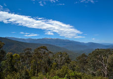 Australian landscape of native trees in snow capped mountains with white clouds and big blue sky. Stock Photos