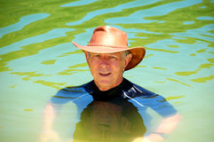 Australian man. A mature man swimming in the cool green waters of Lake Wabby, his leather hat and rashie protecting him from the scorching sun - typical Aussie Royalty Free Stock Photography
