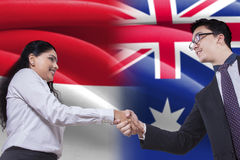 Australian man shaking hands with Indonesian woman Royalty Free Stock Image