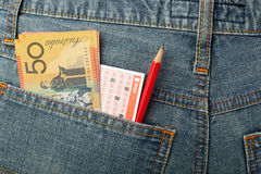 Australian money and lottery betting slip in pocket Stock Image