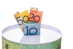 Australian notes stuffed in to a money tin. Austalian notes stuffed in to a money tin on a white background Stock Photography