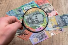 Australian notes under a magnifying glass royalty free stock photo