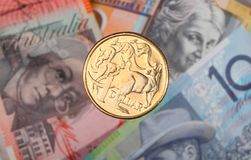 Australian dollar coin and bank notes. An Australian one dollar coin suspended over three bank notes Royalty Free Stock Photo
