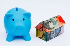Australian Origami Money House with Piggy bank. Origami money house next to a blue Piggy bank Royalty Free Stock Photo
