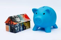 Australian Origami Money House with Piggy bank. Origami money house next to a blue piggy bank Stock Image