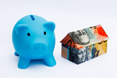 Australian Origami Money House with Piggy bank. Origami money house next to a blue piggy bank Royalty Free Stock Photography