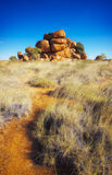 Australian Outback. A path leads through the low scrub to a large pile of rocks in the Australian outback Royalty Free Stock Images