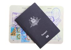 Two Australian passports. Australian passport sitting on an old open passport showing visas on the pages isolated on white background Royalty Free Stock Images