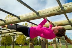 Australian Pull-up. Young woman doing Australian Pull-ups on a jungle gym royalty free stock images