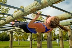 Australian Pull-up. Young woman doing Australian Pull-ups on a jungle gym stock images