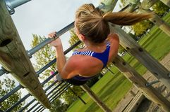 Australian Pull-up. Young woman doing Australian Pull-ups on a jungle gym stock photography