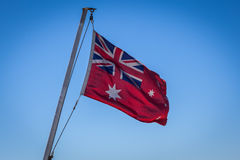 Australian Red Ensign flag on pole against blue sky background. Royalty Free Stock Images