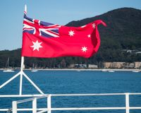 Australian red ensign flag flying from the stern of boat with a natural scene in background. Australian red ensign or maritime flag flying from the stern of a stock photos