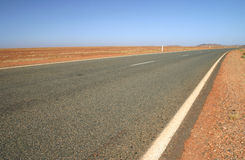 Australian road. Typical Australian road with red dirt and arid landscape. Australia Stock Photos
