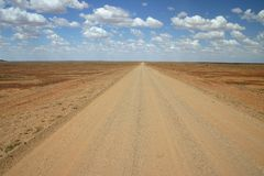 Australian rural road. Against colorful cloudscape sky. Oodnadatta track, South Australia Royalty Free Stock Photography