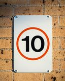 Australian speed road sign for slow 10 km/hr area. Australian speed road sign for ten kilometres an hour with 10 in red circle attached to brown brick wall royalty free stock images