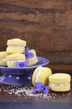 Australian style yo-yo biscuits. Stack of traditional Australian style yo-yo biscuit cookies on purple polka dot stand decorated with violet flowers on dark Stock Image