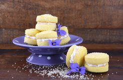 Australian style yo-yo biscuits. Stack of traditional Australian style yo-yo biscuit cookies on purple polka dot stand decorated with violet flowers on dark Royalty Free Stock Image