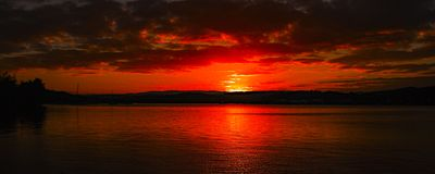 Red colored Cumulus cloud, sunset seascape. Australian Summer seascape, waterscape, sunset with primariley Cumulus clouds against a scarlet and dark grey sky stock photo