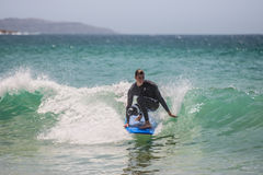Australian surfer catching a small wave Stock Photography
