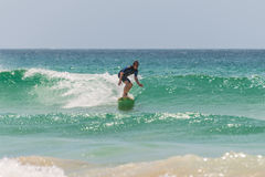 Australian surfer catching a wave Royalty Free Stock Photo
