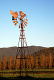 Australian windmill. A rusty windmill sitting on farmland. Sun is setting and blue sky is in background Stock Photography