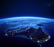 Australien med staden tänder från utrymme på natten Arkivbilder