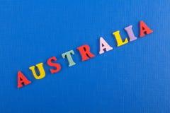 AUSTRALIEN ord på blå bakgrund som komponeras från träbokstäver för färgrikt abc-alfabetkvarter, kopieringsutrymme för annonstext Fotografering för Bildbyråer