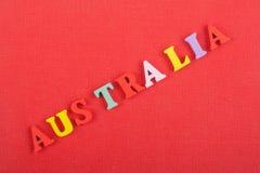 AUSTRALIEN ord på röd bakgrund som komponeras från träbokstäver för färgrikt abc-alfabetkvarter, kopieringsutrymme för annonstext Arkivbilder