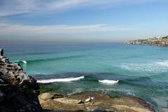 Australien: Sikt för Tamarama strandstad med surfare Arkivbild