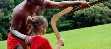 Australier Aboriginalsmann bringt einem jungen Mädchen bei, wie man a wirft lizenzfreie stockbilder