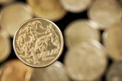 Australier eine Dollar-Münze über unscharfem goldenem Hintergrund Stockfotografie