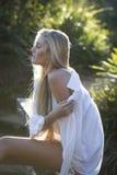 Australier mit dem langen blonden Haar, das auf Brücke sitzt, schaut über ihrer Schulter Lizenzfreie Stockbilder
