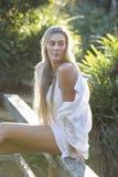 Australier mit dem langen blonden Haar, das auf der Brücke weg schaut sitzt Stockfotos
