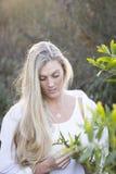 Australier mit langem blondes Haar-rührendem Baum Lizenzfreies Stockfoto