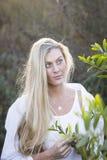 Australier mit langem blondes Haar-rührendem Baum stockfoto