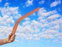 Australijski bumerang w mężczyzna ręce przeciw chmurnemu niebieskiemu niebu Fotografia Stock