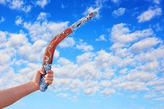 Australijski bumerang w mężczyzna ręce przeciw chmurnemu niebieskiemu niebu Obraz Royalty Free