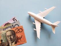 australische Banknoten, weißes Plastikflugzeug und blauer Hintergrund stockfotografie