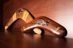 Australische Bumerangs gesehen von der Seite, liegend auf dem Weinlesebraunregal Andenken von Australien auf Anzeige im Wohnzimme lizenzfreie stockfotografie