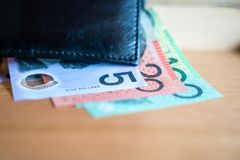 Australische Dollars 5, 20, 100 dollarsnota's en rekeningen naast zwarte portefeuille in selectief nadruk$ Royalty-vrije Stock Foto's